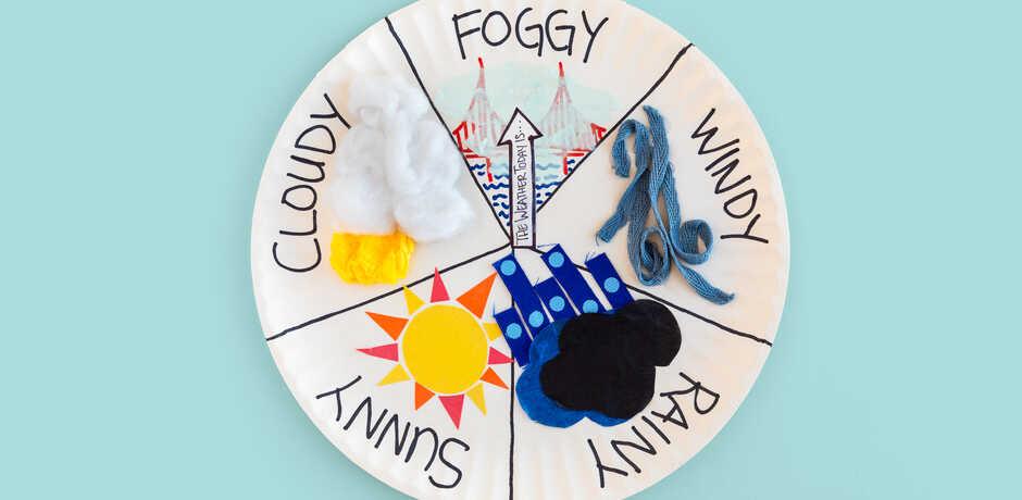 Handmade weather wheel against light blue background