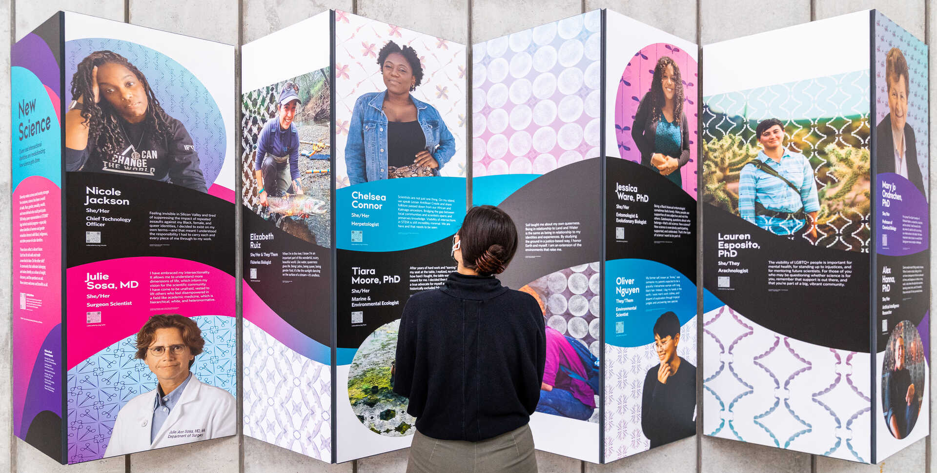 Guest looks at New Science exhibit panel featuring portraits of LGBTQ+ scientists