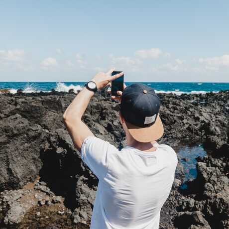 Man on rocky coastline takes picture with mobile phone
