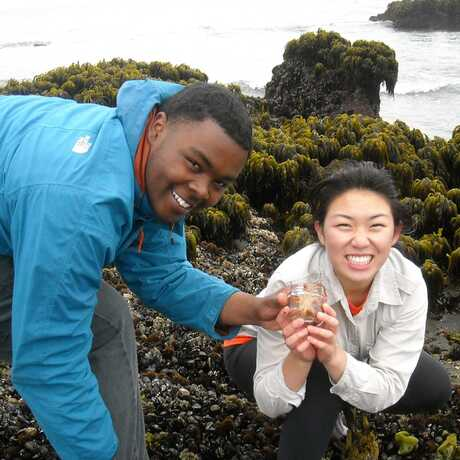 2 smiling high school students display a specimen on a rocky tidepool