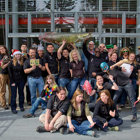 A group of staff goof off for the camera in front of the Academy staff entrance