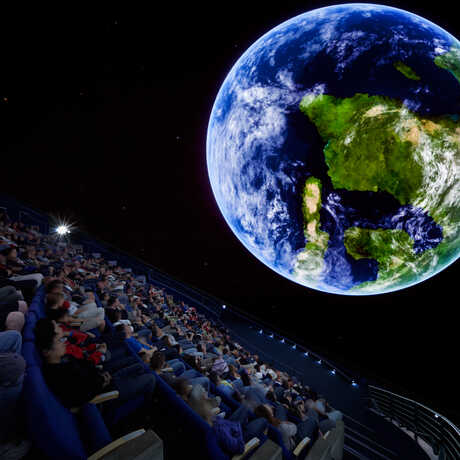 Audience inside Morrison Planetarium with Earth projected on screen
