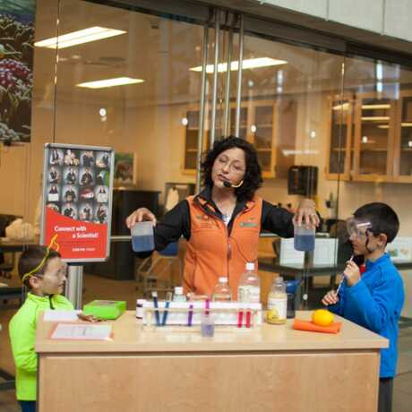 Academy docent demonstrates science experiment to young guests